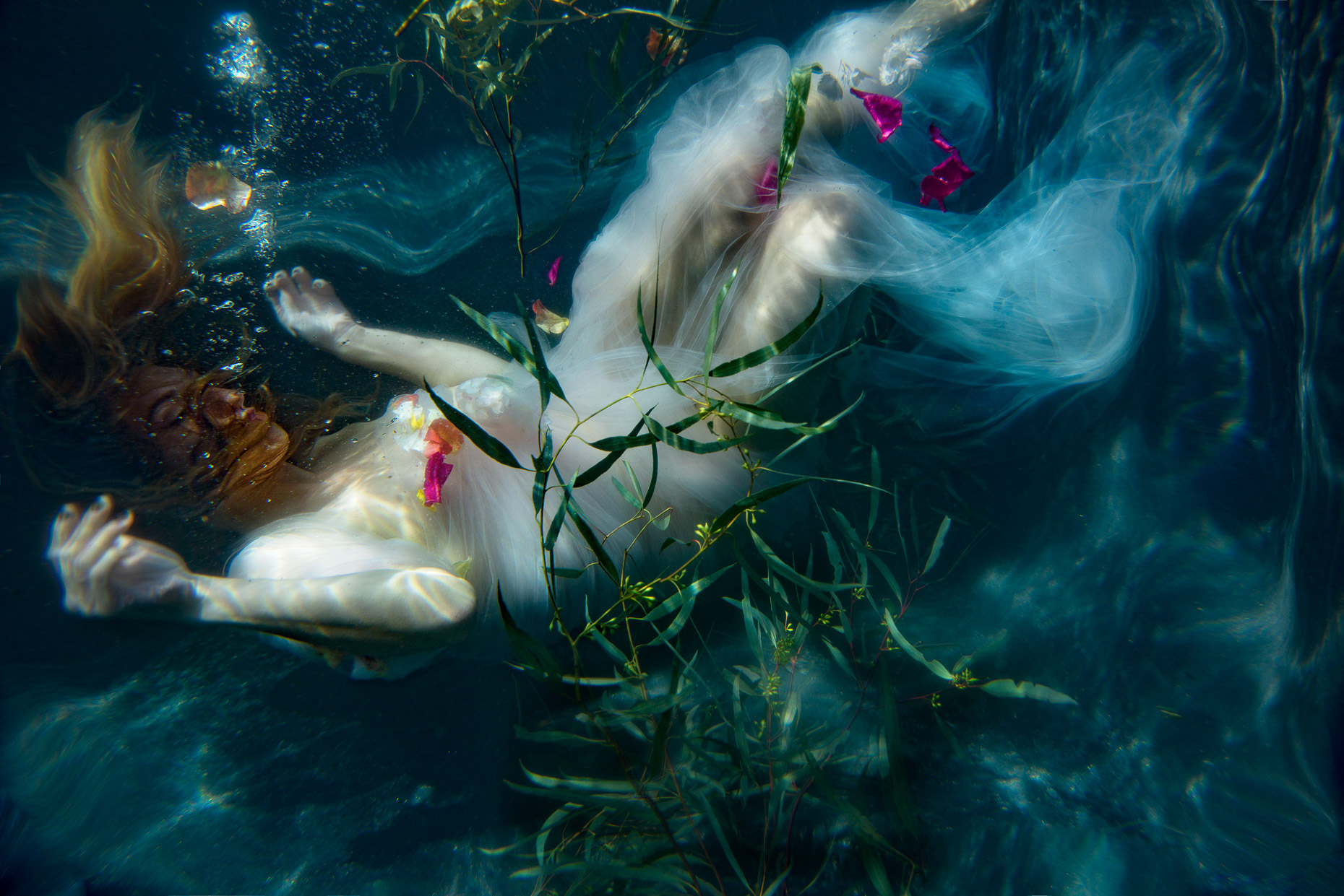 Portrait underwater woman in white dress with plants and flowers