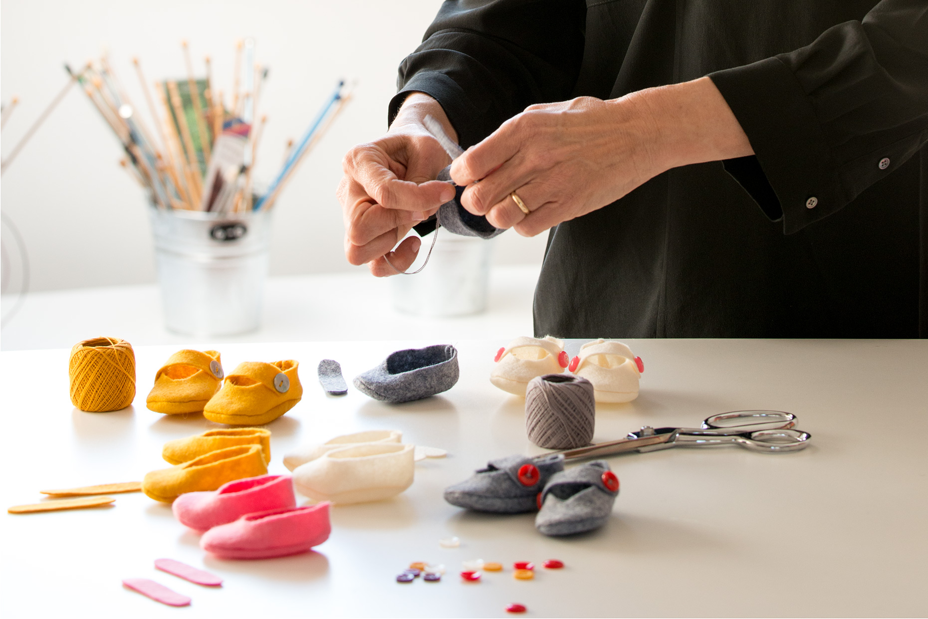 Photographer for business websites hands making doll shoes