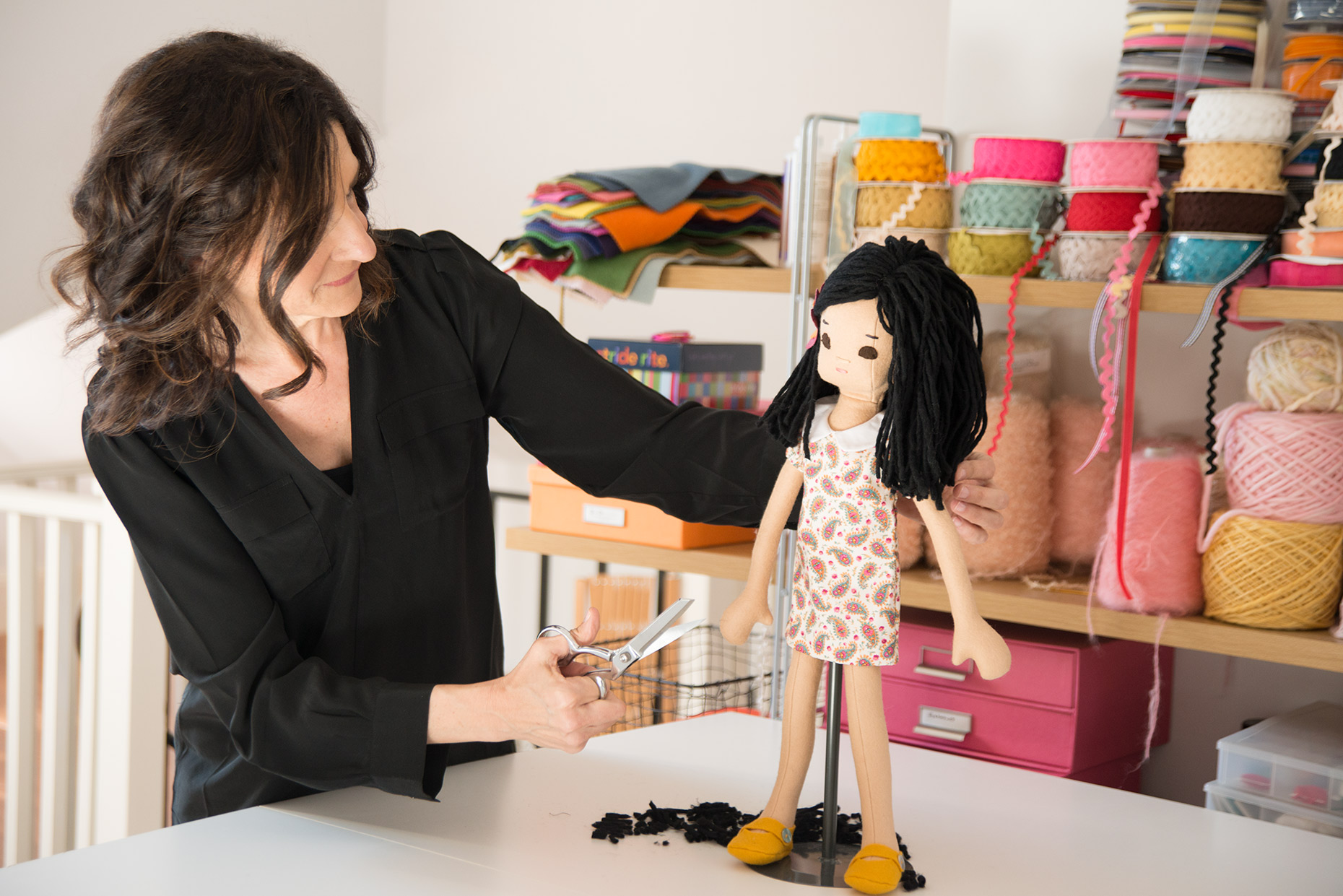 Product photography with context doll maker working at her table