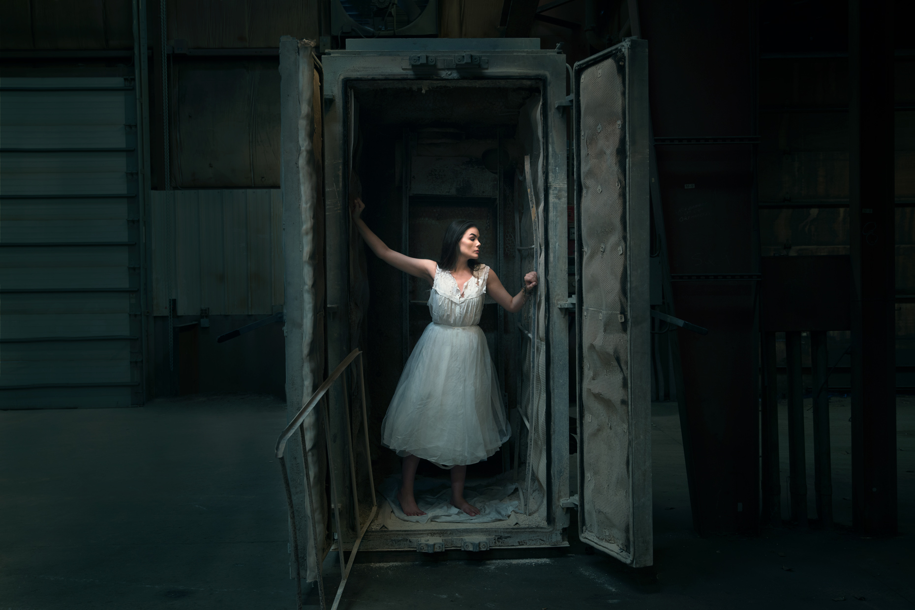Portrait fine art photographer woman in white escaping a box